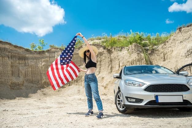 Séance photo d'une charmante dame avec le drapeau américain près de la voiture dans une carrière de sable en été