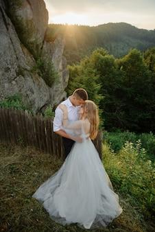 Séance photo d'un couple amoureux dans les montagnes. la jeune fille est habillée comme une mariée dans une robe de mariée.