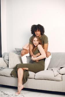 Séance photo heureux jeune couple à la maison sur le canapé. étreindre, s'embrasser.