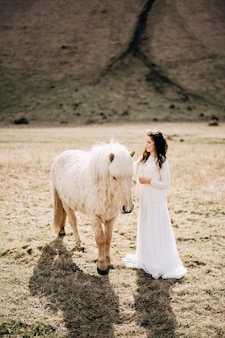Séance photo de mariage à destination de l'islande avec des chevaux islandais la mariée en robe blanche caressant