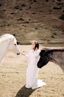 Séance photo de mariage à destination de l'islande avec des chevaux islandais, une mariée en robe blanche se promène parmi