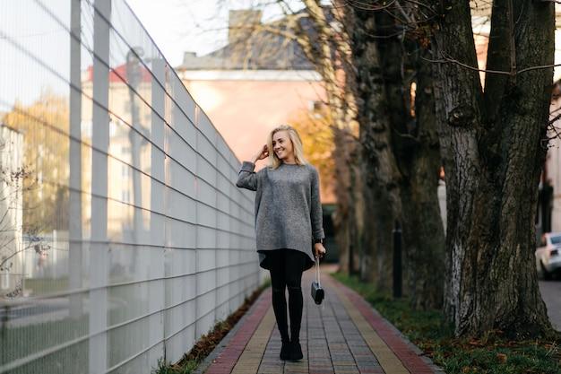 Séance photo de mode rue de la jeune femme élégante dans un vêtement gris