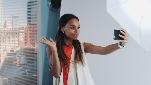 En séance photo pause beau modèle africain faisant selfie sur smartphone en studio professionnel