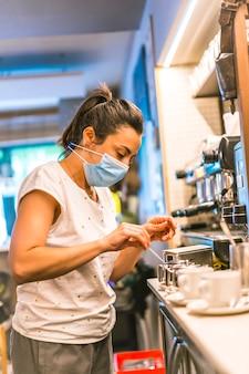 Séance photo avec une serveuse avec un masque dans un bar. préparer une coupe de café au lait avec la machine