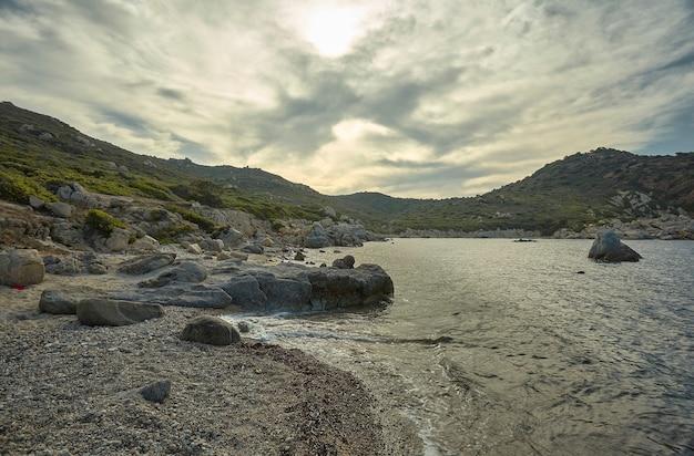 Seascape al tramonto contenente una magnifica spiaggia mediterranea con i promontori rocciosi e le montagne sotto un cielo nuvoloso con spiragli di sole.