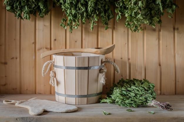 Un seau en bois et un balai en bouleau dans un bain russe. sauna.