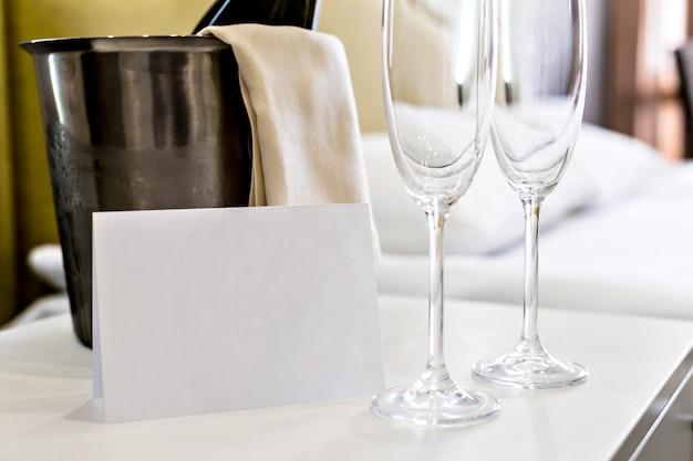 Seau à champagne près du lit dans une chambre d'hôtel