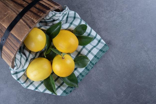 Seau de citrons frais sur fond gris.