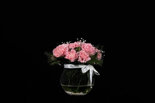 Seau de fleurs d'oeillets roses dans un vase en verre sur fond noir
