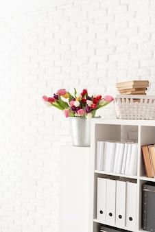 Seau de fleurs de tulipes fraîches à côté de l'étagère sur fond de mur de brique blanche