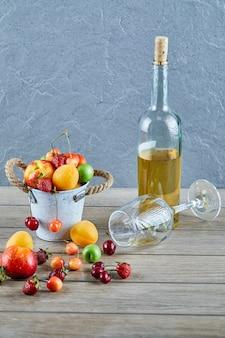 Seau de fruits frais d'été, bouteille de vin blanc et verre vide sur table en bois.
