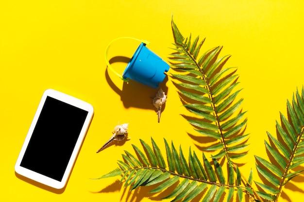 Seau de gadget et feuille de palmier sur fond clair