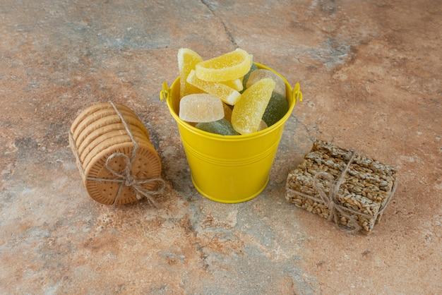 Un seau jaune de marmelade avec des biscuits et des brittles d'arachide