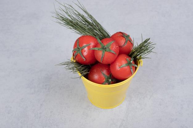 Seau jaune avec des tomates sur fond sombre