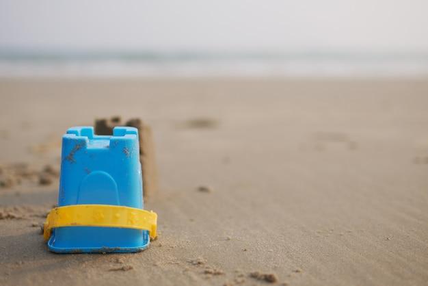 Seau de jouet d'enfant sur la plage de sable