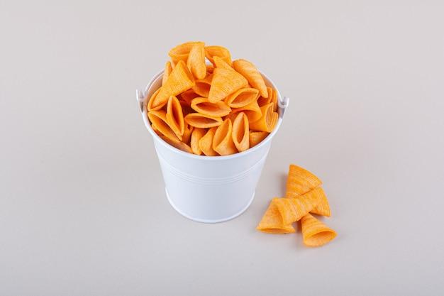 Seau en métal de chips triangulaires sur fond blanc. photo de haute qualité