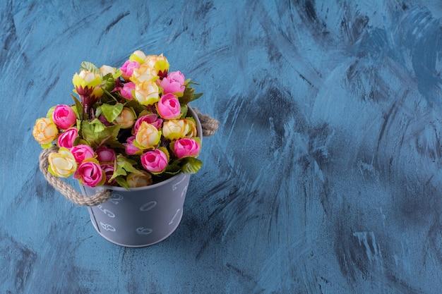 Seau en métal de composition florale colorée sur bleu.