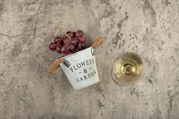 Seau en métal de raisins frais rouges et verre de vin blanc sur une surface en marbre.
