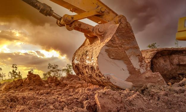 Seau en métal sale de la pelle rétrocaveuse après avoir creusé le sol. pelle rétro garée sur une terre agricole sur ciel coucher de soleil. pelle sur chenilles. machine de terrassement sur chantier au crépuscule. véhicule d'excavation.