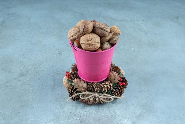 Seau de noix et une couronne de pomme de pin sur marbre.