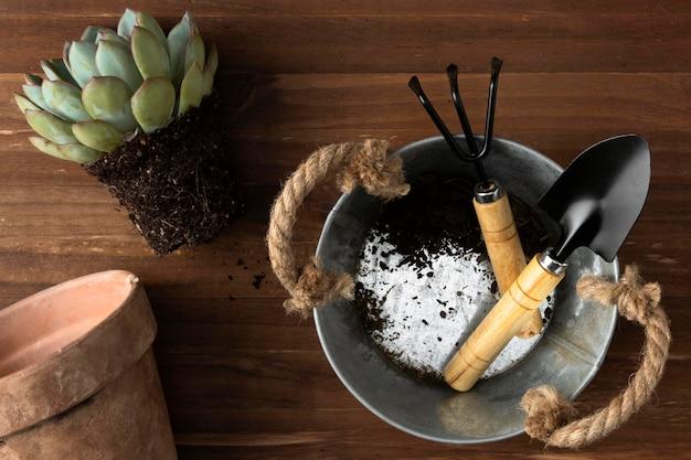 Seau avec outils de jardinage sur marbre