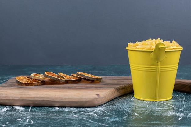 Seau de pâtes penne et tranches d'orange sur fond bleu. photo de haute qualité