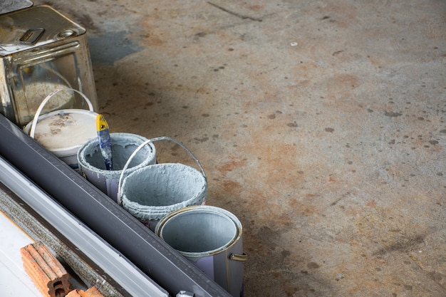 Le seau de peinture est déjà utilisé sur un sol en béton sur un chantier de construction.