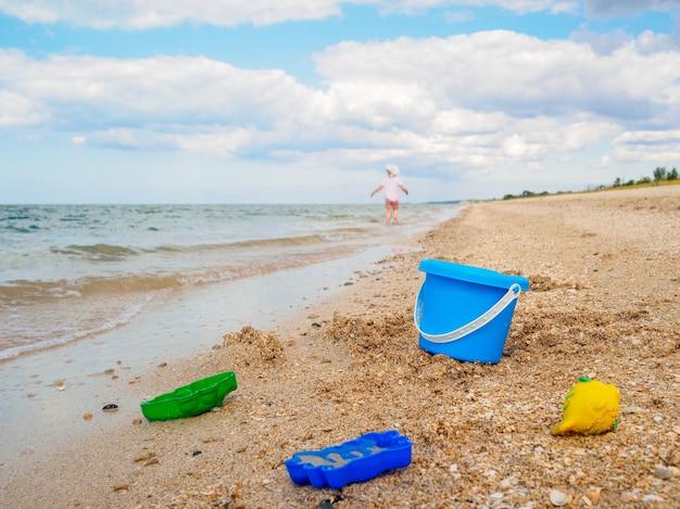 Un seau en plastique bleu et des jouets dans le sable au bord de la mer du ciel et une petite fille s'enfuyant dans la distance