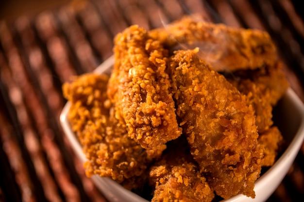 Seau plein de poulet frit kentucky croustillant avec de la fumée sur fond marron. mise au point sélective.