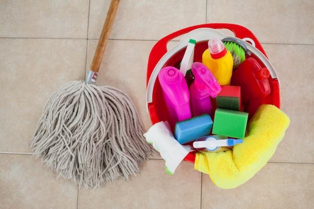Seau avec des produits de nettoyage et une vadrouille sur un sol en carrelage