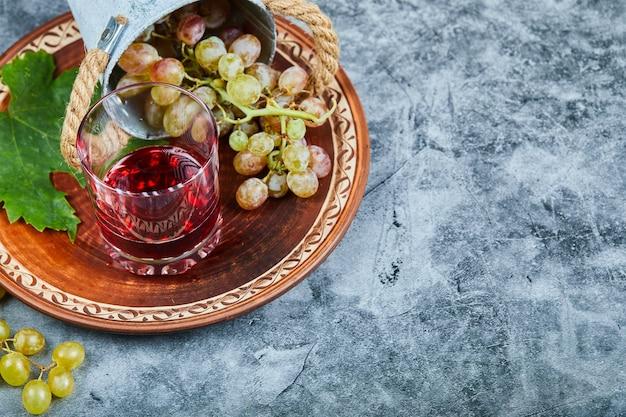 Seau de raisins et un verre de jus sur marbre.