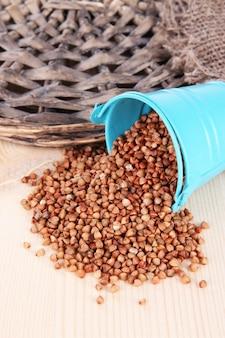 Seau renversé avec des grains sur fond de bois