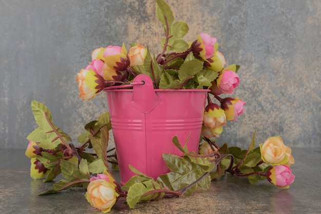 Un seau rose avec bouquet de fleurs sur une surface en marbre.