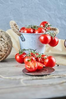 Seau de tomates et tomates coupées à moitié sur table en bois.
