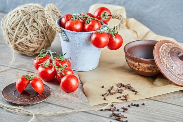 Seau de tomates et tomates coupées à moitié sur table en bois