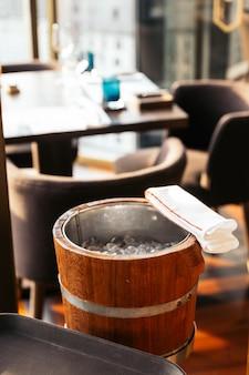 Seau à vin en bois avec tissu blanc. préparez-vous à refroidir certains vins.