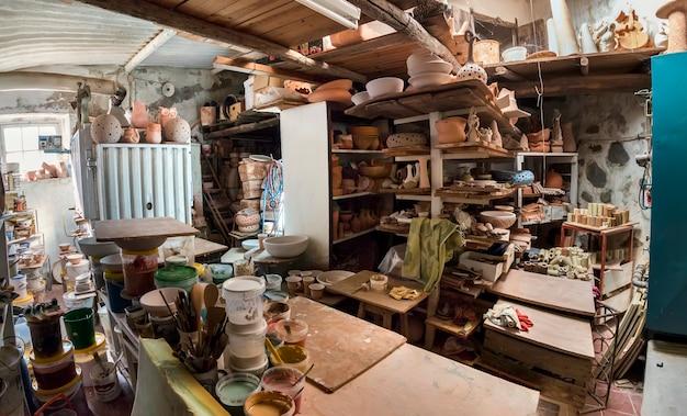 Seaux de peinture et brosses usés dans un atelier de céramique