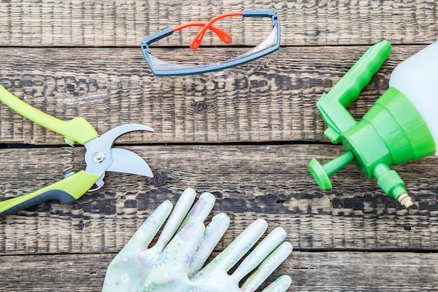 Sécateur, pulvérisateur à pression, gants de jardin et lunettes de protection sur planche de bois. outils et équipement de jardin