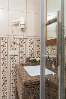 Sèche-cheveux au mur dans la salle de bain