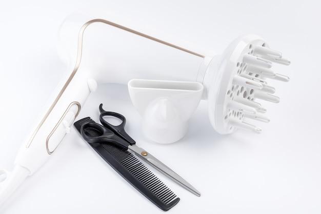 Sèche-cheveux avec différents accessoires, ciseaux et peigne sur fond blanc.