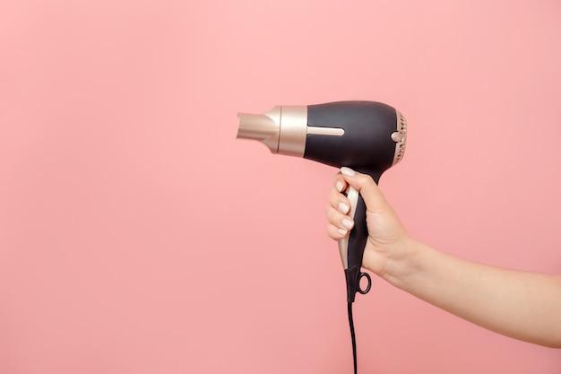 Sèche-cheveux à la main de femme