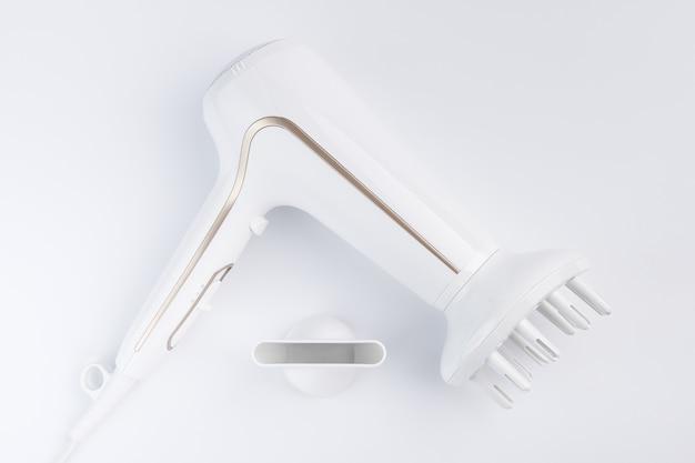 Sèche-cheveux pour sécher les cheveux avec une buse diffuse et plate pour le coiffage sur fond blanc. vue de dessus.