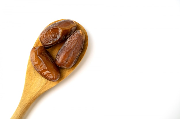 Séché de fruits de palmier doux dates sur la cuillère en bois sur fond blanc.