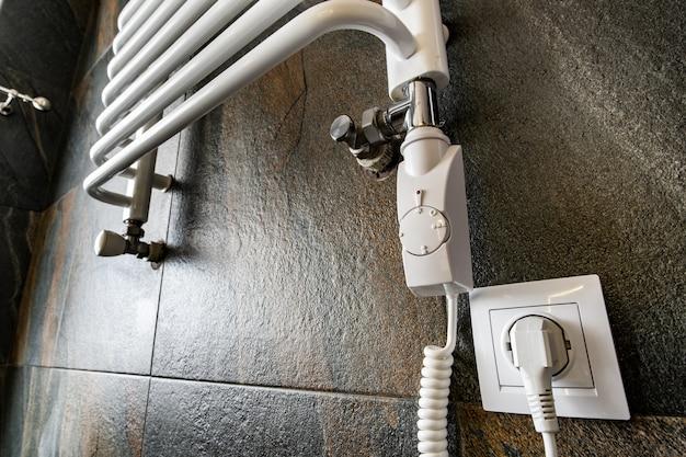 Sèche-serviettes électrique contemporain blanc monté sur un mur carrelé noir dans une salle de bain moderne.