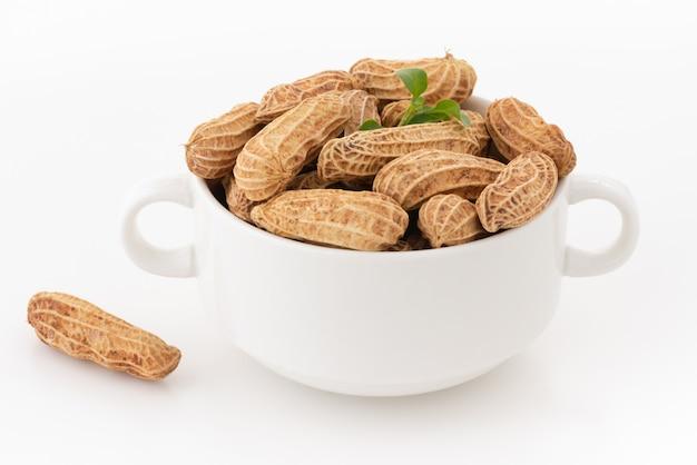 Sécher les cacahuètes dans un bol blanc sur blanc isolé