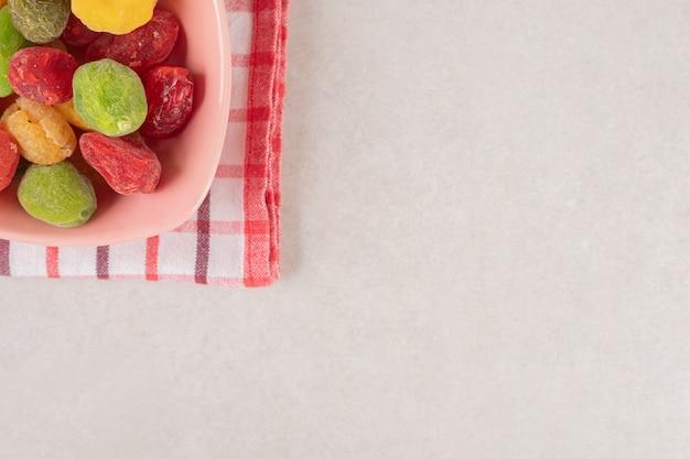 Sécher les cerises colorées dans une tasse en céramique.