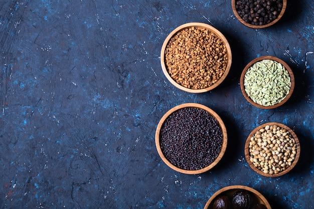 Sécher les épices indiennes entières dans des bols en bois sur fond rustique en béton bleu foncé.