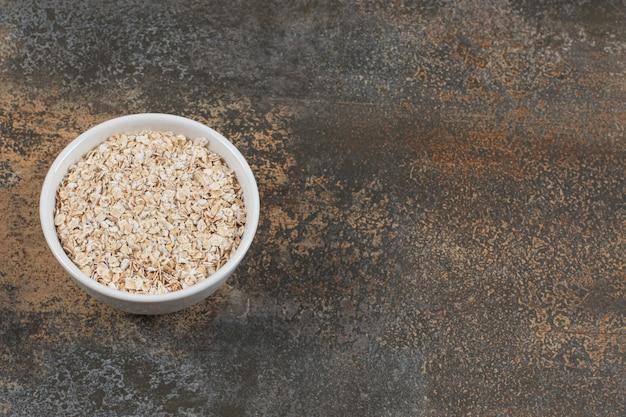 Sécher les flocons d'avoine dans un bol blanc.