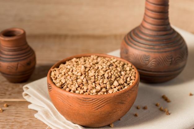 Sécher le sarrasin dans un bol d'argile brune sur une table en bois. grain sans gluten pour une alimentation saine