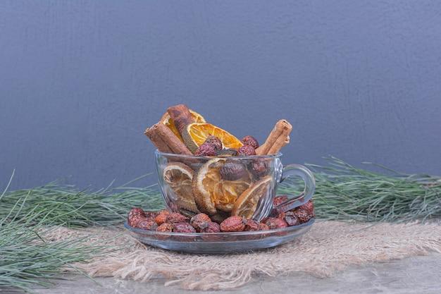 Sécher les tranches d'oranges et les hanches avec des bâtons de cannelle dans une tasse en verre